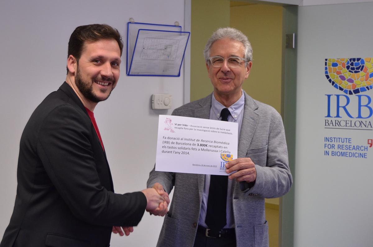 Xavier Ayala entrega el xec de 3.800 euros a Joan Josep Guinovart, director de l'IRB. Foto: Institut de Recerca Biomèdica de Barcelona